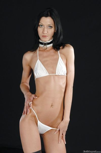 Skinny brunette in latex high heeled boots slipping off her bikini